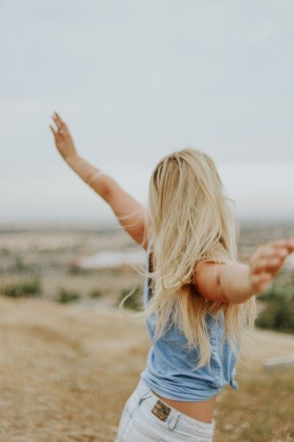 Woman With Arms Raised on Beach